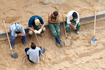Sitting workers with shovels on the rest, fotolia